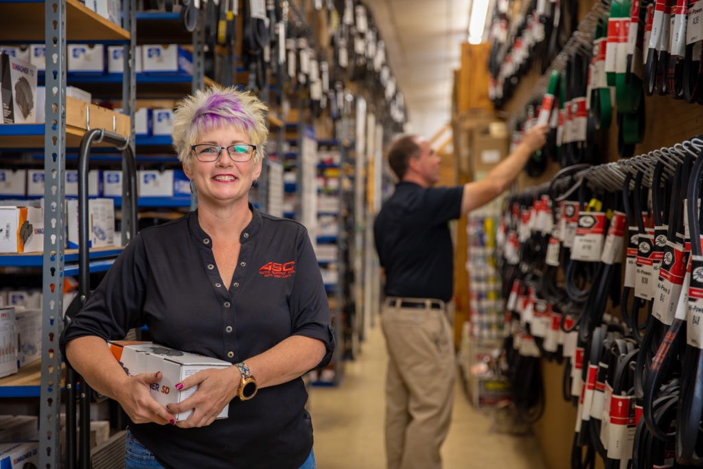 woman holding an auto part in front of shelves of auto parts with a man picking a part from the shelf in the background